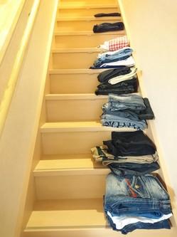 階段に服が積まれていく
